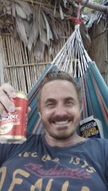 Thomas drikker øl i hengekøya